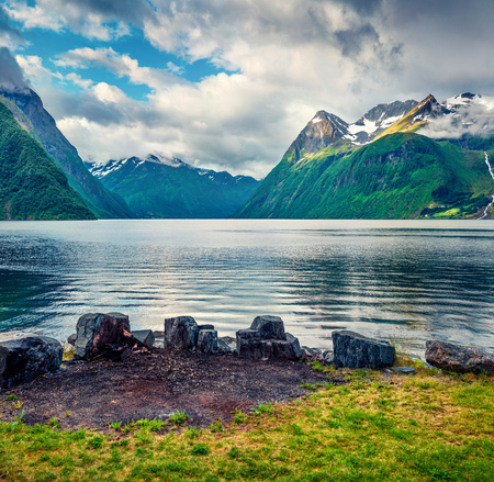 Dramatic summer scene of Hjorundfjorden fjord, Orsta municipality, More og Romsdal county. Great morning view of Norway. Beauty of nature concept background.