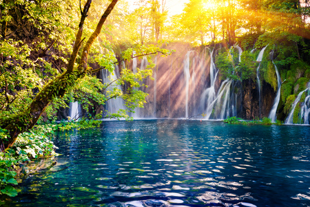 Last sunlight lights up the pure water waterfall on Plitvice National Park. Colorful spring scene of green forest with blue lake. Great countryside view of Croatia, Europe. Beauty of nature concept background.