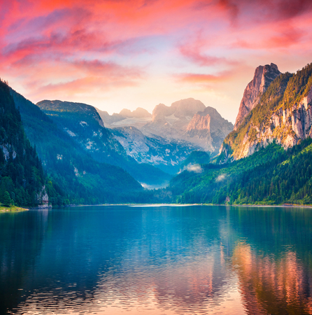 Dramatic summer sunrise on Vorderer ( Gosausee ) lake. Impressive morninf scene of Austrian Alps. Upper Austria, Europe. Beauty of nature concept background. Stock Photo