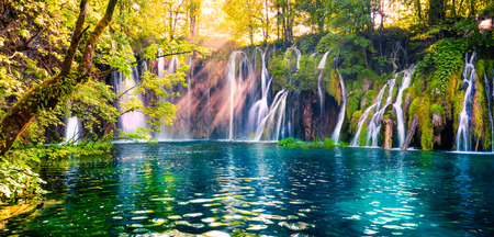 Last sunlight lights up the pure water waterfall on Plitvice National Park. Colorful spring panorama of green forest with blue lake. Great countryside view of Croatia, Europe. Beauty of nature concept background.
