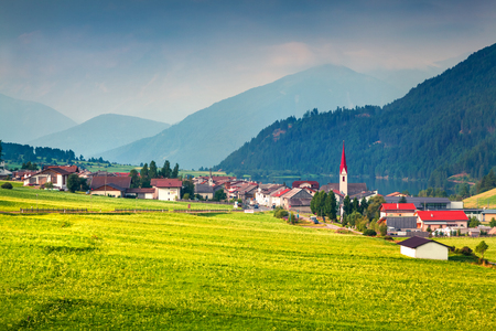 Dramatic summer view of St. Valentin village. Picturesque morning scene of Muta lake (Haidersee), South Tyrol, Italy, Europe. Beauty of countryside concept background. Foto de archivo - 116549837