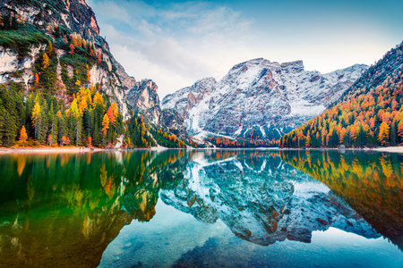 First snow on Braies Lake. Colorful autumn landscape in Italian Alps, Naturpark Fanes-Sennes-Prags, Dolomite, Italy, Europe. Beauty of nature concept background. Imagens