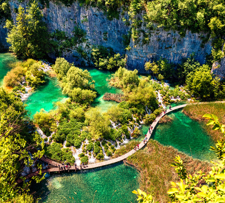 Aerial morning wiew of Plitvice National Park. Colorful spring scene of turists walking on the bridge in green forest with lakes and waterfalls. Great countryside view of Croatia, Europe. Traveling concept background.