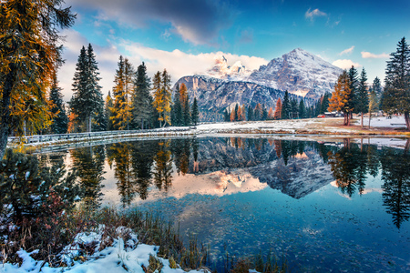 Majestic sunrise on Antorno lake with Cristallo mountain range on background. Picturesque autumn morning in Dolomite Alps, Province of Belluno, Italy, Europe. Traveling concept background.