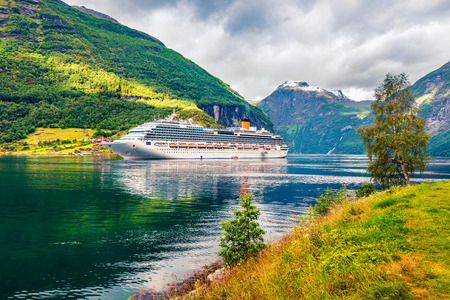 Sunny summer scene of Geiranger port, western Norway. Colorful view of Sunnylvsfjorden fjord. Traveling concept background. Artistic style post processed photo. Stock Photo