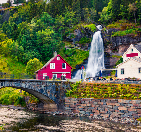 Splendid summer view with Large, popular waterfall Steinsdalsfossen on the Fosselva River. Picturesque morning scene of  village of Steine village, municipality of Kvam in Hordaland county, Norway.