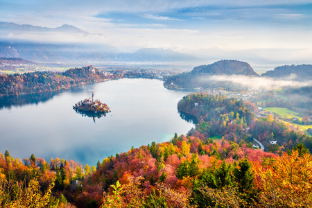 Aerial view of church of Assumption of Maria on the Bled lake. Foggy autumn landscape in Julian Alps, Slovenia, Europe. Beauty of countryside concept background. Stok Fotoğraf - 116549993