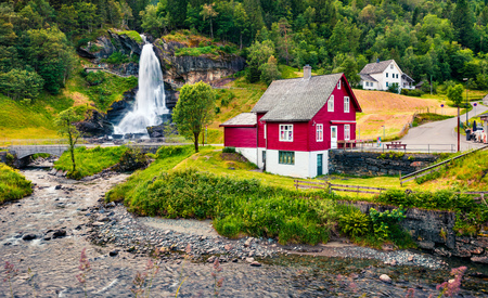 Great summer view with Large, popular waterfall Steinsdalsfossen on the Fosselva River. Picturesque morning scene of  village of Steine village, municipality of Kvam in Hordaland county, Norway.