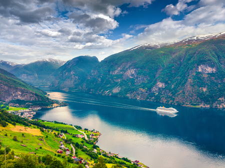 Awesome summer view of Sognefjorden fjord. Colorful morning scene with Aurlandsvangen village, Norway. Traveling concept background. Artistic style post processed photo.