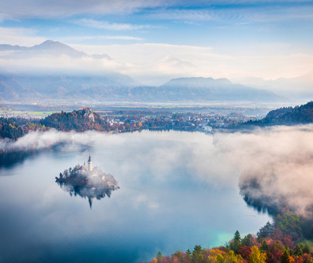 Aerial view of church of Assumption of Maria on the Bled lake. Foggy autumn landscape in Julian Alps, Slovenia, Europe. Beauty of countryside concept background.