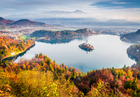 Impressive view of church of Assumption of Maria on the Bled lake. Foggy autumn landscape in Julian Alps, Slovenia, Europe. Beauty of countryside concept background.