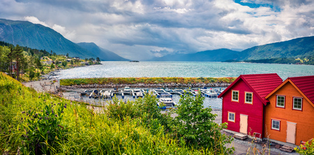 Picturesque summer view of typical Norwegian village on the shore of fjord. Traveling concept background. Artistic style post processed photo. Stock Photo