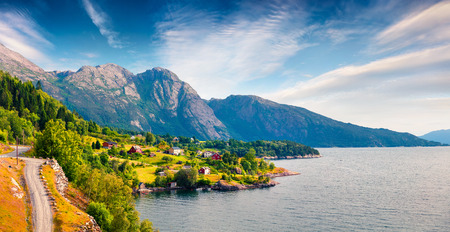 Picturesque summer panorama of typical Norwegian village on the shore of fjord. Traveling concept background. Artistic style post processed photo. Stock Photo