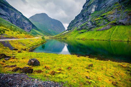 Rainy summer scene of Stavbergvatnet lake, located near Hjorundfjorden fjord, Orsta municipality, More og Romsdal county. Great morning view of Norway. Beauty of nature concept background. Foto de archivo - 116550588