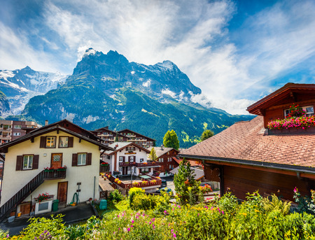 Colorful morning view of Grindelwald village. Great summer scene of Wetterhorn mountain, located west of Innertkirchen in the Bernese Oberland Alps. Switzerland, Europe. Traveling concept background.