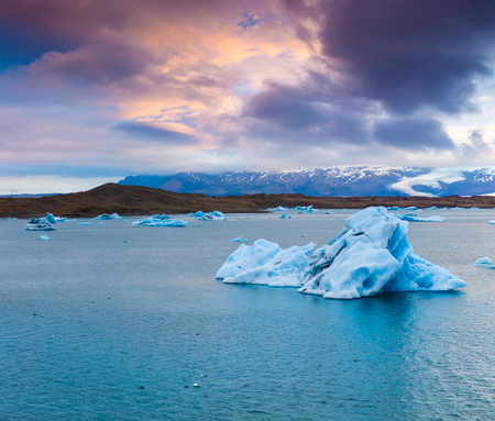 Floating of blue icebergs in Jokulsarlon glacial lagoon. Colorful sunset in Vatnajokull National Park, southeast Iceland, Europe. Beauty of nature concept background.
