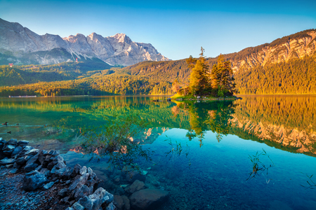 Colorful summer sunrise on the Eibsee lake with Zugspitze mountain range. Picturesque outdoor scene in German Alps, Bavaria, Garmisch-Partenkirchen village location, Germany, Europe. Foto de archivo - 116550650