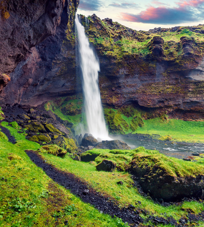 Colorful morning view from the middle of Kvernufoss waterfall. Majestic summer scene of south Iceland, Europe. Beauty of nature concept background.