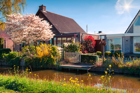 Sunny spring view of the typical Dutch countryside. Colorful morning scene in the small town Alblasserdam, located near famous windmills museum - Kinderdijk, Netherlands, Europe. Imagens