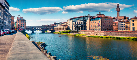 Sunny spring cityscape of Florence with Old Palace (Palazzo Vecchio or Palazzo della Signoria) on background and Ponte Vecchio bridge over Arno river. Colorful morning panorama of Italy, Europe.