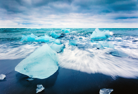 Blocks of ice washed by the waves on Jokulsarlon beach. Dramatic summer scene of Vatnajokull National Park, southeast Iceland, Europe. Beauty of nature concept background. Stock fotó