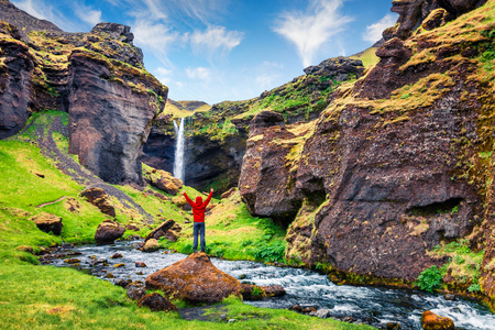 Colorful morning view of Kvernufoss waterfall. Picturesque scene in south Iceland with tourist standing on the rock. Traveling concept background. Reklamní fotografie