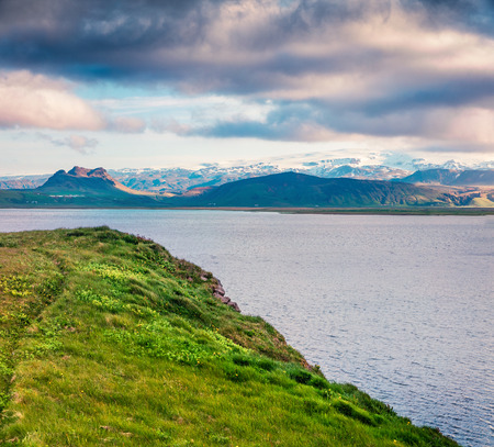 Typical Icelandic landscape with volcanic mountains and Atlantic ocean coast. Sunny summer morning in the west coast of Iceland, Europe. Beauty of nature concept background.