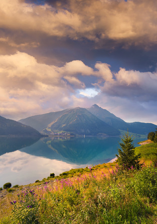 Unbelievable summer sunrise on Resia (Reschensee) lake. Great morning view of Curon Venosta village, Alps, Italy, Europe. Beauty of nature concept background. Stock Photo