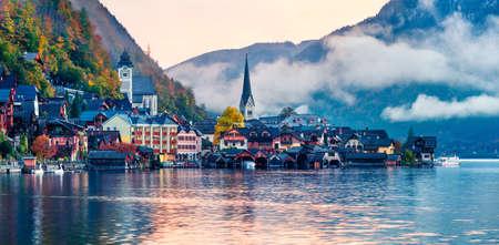 Alba nebbiosa di autunno sul lago Hallstatt. Pittoresco panorama mattutino del villaggio di Hallstatt, nella regione montuosa del Salzkammergut, Austria. Bellezza dello sfondo del concetto di campagna.