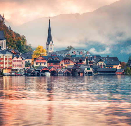 Foggy autumn sunrise on Hallstatt lake. Spectacular morning view of Hallstatt village, in Austria's mountainous Salzkammergut region, Austria. Beauty of countryside concept background.