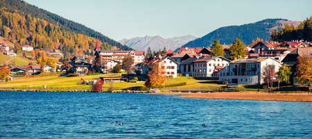 Panoramic autumn view of San Valentin village. Colorful morning scene of small Italian village located on shore of Muta lake, South Tyrol, Italy, Europe. Beauty of countryside concept background. Foto de archivo - 116551629