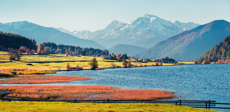 Spectacular autumn scene of Haidersee (Lago della Muta) lake with Ortler peak on background. Splendid morning view of Italian Alps, Italy, Europe. Beauty of countryside concept background.