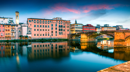 Attractive medieval arched St Trinity bridge (Ponte Santa Trinita) over Arno river. Colorful spring sunset in Florence, Italy, Europe. Traveling concept background.