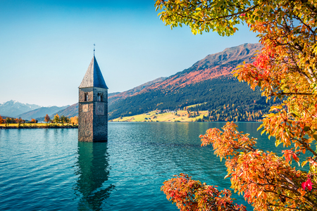 Impressive autumn view of Tower of sunken church in Resia lake. Amazing morning scene of Italian Alps, South Tyrol, Italy, Europe. Traveling concept background. Foto de archivo - 116551644