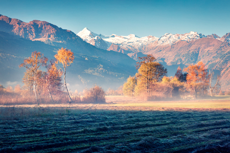 Foggy morning scene near Zell lake. Sunny autumn view of Austrian Alps, with Grossglockner peak on background. Beauty of nature concept background. Stock Photo