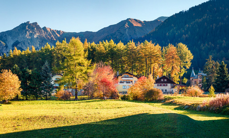 Colorful autumn view of San Valentin village. Beautufel morning scene of small Italian village located on shore of Muta lake, South Tyrol, Italy, Europe. Beauty of countryside concept background.
