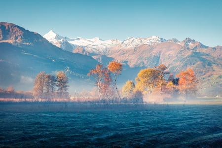 Misty morning scene near Zell lake. Picturesque autumn view of Austrian Alps, with Grossglockner peak on background. Beauty of nature concept background. Stock Photo