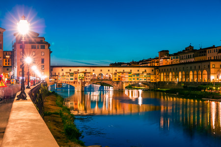 Fantastic evening cityscape of Florence with Old Palace (Palazzo Vecchio or Palazzo della Signoria) on background and Ponte Vecchio bridge over Arno river. Colorful night scene of Italy, Europe.