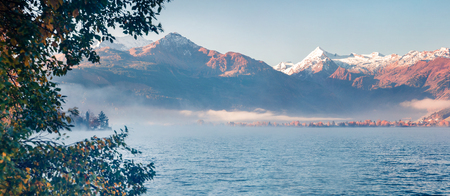 Misty morning panorama of Zell lake. Picturesque autumn view of Austrian Alps, with Grossglockner peak on background. Beauty of nature concept background.