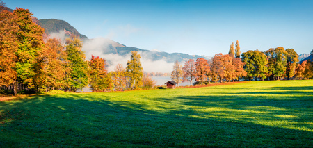 Magnificent autumn scene of Kurpark in Thumersbach village, located on the shore of the Zell lake. Colorful morning panorama of Austrian Alps, Europe. Beauty of countryside concept background.