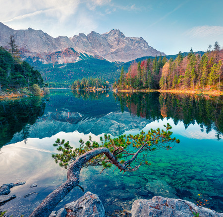 Splendid morning scene of Eibsee lake with Zugspitze mountain range on background. Colorful autumn view of Bavarian Alps, Germany, Europe. Beauty of nature concept background. Stock Photo