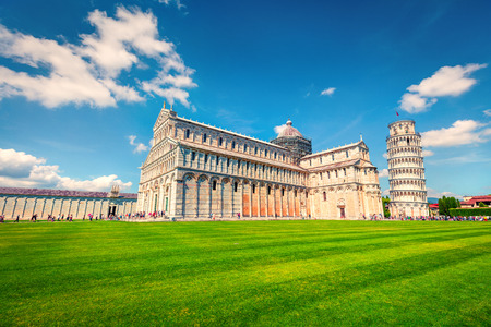 Captivating spring view of famous Leaning Tower in Pisa. Sunny morning scene with hundreds of tourists in Piazza dei Miracoli (Square of Miracles), Italy, Europe. Traveling concept background.