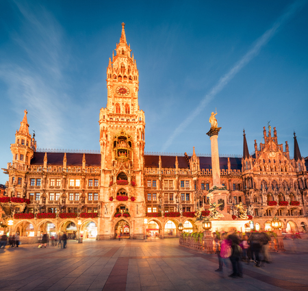 Impressive evening view of Marienplatz - City-center square & transport hub with towering St. Peters church, two town halls and a toy museum, Munich, Bavaria, Germany, Europe.