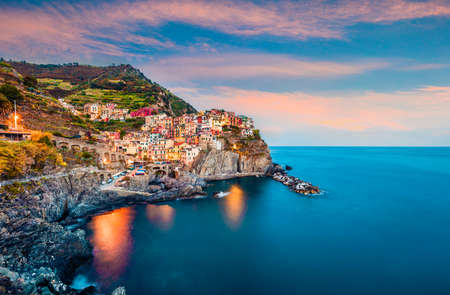 Second city of the Cique Terre sequence of hill cities - Manarola. Colorful spring sunset in Liguria, Italy, Europe. Picturesqie seascape of Mediterranean sea. Traveling concept background. Foto de archivo - 116551804