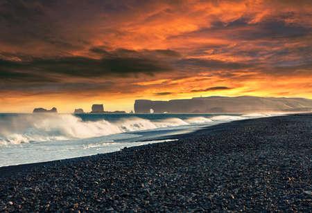 Stormy weather on the Kirkjufjara beach. Dramatic summer sunset on Dyrholaey arch, south coast of Iceland, Europe. Impressive Atlantic seascape. Beauty of nature concept background.
