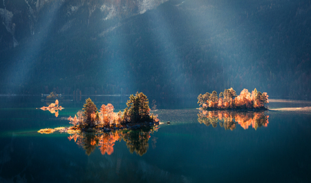 Unbelievable autumn scene of Eibsee lake. Dramatic morning view of first sunlight glowing small islands on bottom of the Zugspitze peak, Bavaria, Germany, Europe. Beauty of nature concept background.