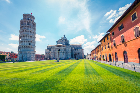 Beautiful spring view of famous Leaning Tower in Pisa. Sunny morning scene with hundreds of tourists in Piazza dei Miracoli (Square of Miracles), Italy, Europe. Traveling concept background.
