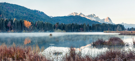 Splendid morning panorama of Wagenbruchsee (Geroldsee) lake with Zugspitze mountain range on background. Beautiful autumn view of Bavarian Alps, Germany, Europe. 写真素材