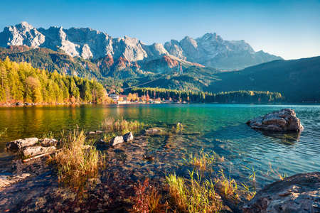 Marvelous evening scene of Eibsee lake with Zugspitze mountain range on background. Exciting autumn view of Bavarian Alps, Germany, Europe. Beauty of nature concept background. 스톡 콘텐츠