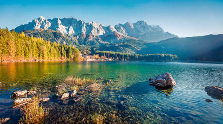 Sunny evening scene of Eibsee lake with Zugspitze mountain range on background. Beautifel autumn view of Bavarian Alps, Germany, Europe. Beauty of nature concept background.